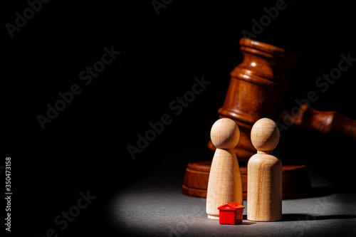 Divorse property division concept. Wooden family with house and judge gavel close up