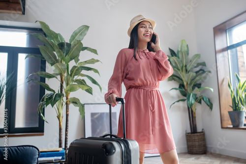 Dark-haired female in straw hat standing, holding suitcase handle and talking on mobile phone