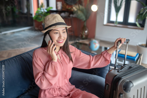 Dark-haired female in straw hat talking on mobile phone, sitting on sofa, holding suitcase handle