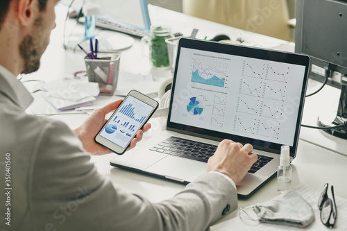 Over shoulder view of businessman using smartphone and laptop while analyzing sa Fototapet