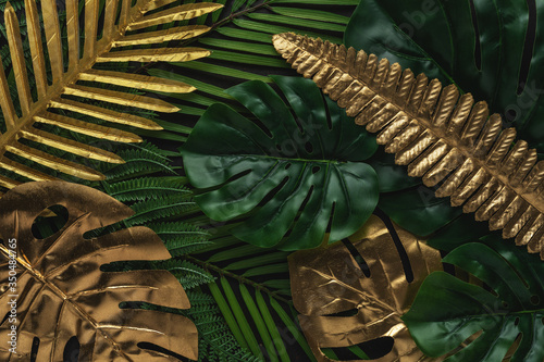 Obraz Creative layout with gold and green tropical palm leaves on black background. Minimal summer abstract pattern. - fototapety do salonu