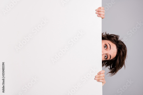 Obraz Closeup photo of funny pretty lady holding hands empty paper poster proposing advert place look interested peeking eyes tricky crazy person isolated grey color background - fototapety do salonu