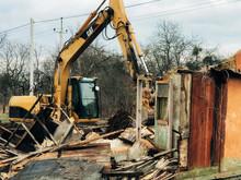 Excavator Destroying Brick Hou...