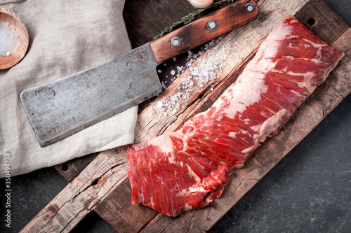 Cuadros en Lienzo Raw beef machete steak with meat axe on a wooden Board with seasoning