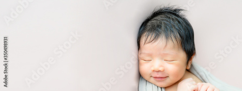Fotografia Panorama image of an adorable cute smiling Asian newborn baby sleeping