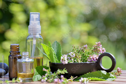 Fototapeta bottles of essential oil and flowers of aromatic herb on atable and on green bac