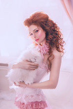 Woman In Stylish Clothes Vintage White Dress, Baroque Frill, Bow. Art Style Photo. Rococo High Hairstyle Red Curly Hair. Lady Holds Rabbit Animal. Sexy Face Pink Lip Carnival Makeup Mole. Classic Room