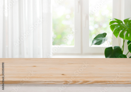 Obraz Wooden table top for product display over blurred curtained window - fototapety do salonu