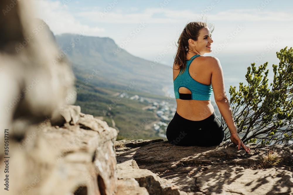 Fototapeta Woman hiker relaxing in the cliff