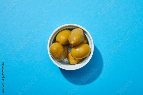 Fototapeta top view of olives in bowl on blue colorful background obraz