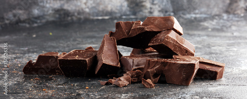 Photo close up of bitter chocolate bars and broken piesces on rustic background