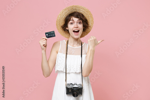 Fotografering Excited young tourist girl in dress hat with photo camera isolated on pink background