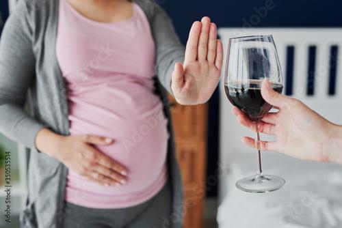 Valokuvatapetti Pregnant woman refusing a glass of wine