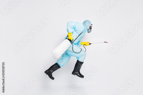 Obraz Full body profile side photo man jump run hurry disinfect covid spread house wear white hazmat suit yellow rubber latex gloves goggles use sprayer isolated gray color background - fototapety do salonu
