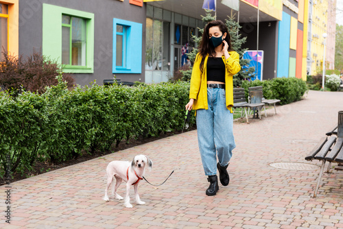 Obraz attractive woman in black medical mask walking with chinese crested dog in city - fototapety do salonu