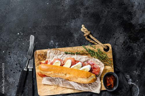 Fotomural baguette sandwich with jamon ham serrano, paleta iberica, Camembert cheese on the cutting Board