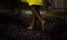 Low Section Of Man Running Barefoot On Hot Coals