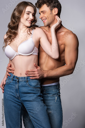 happy girl touching shirtless boyfriend and smiling on grey