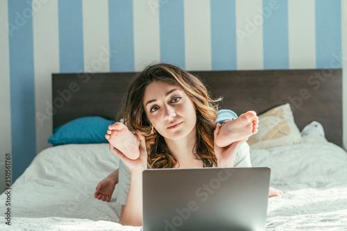 Fototapeta freelancer touching legs of toddler son near laptop on bed obraz