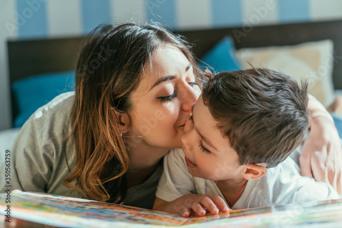 Photo attractive mother kissing cheek of cute toddler boy at home