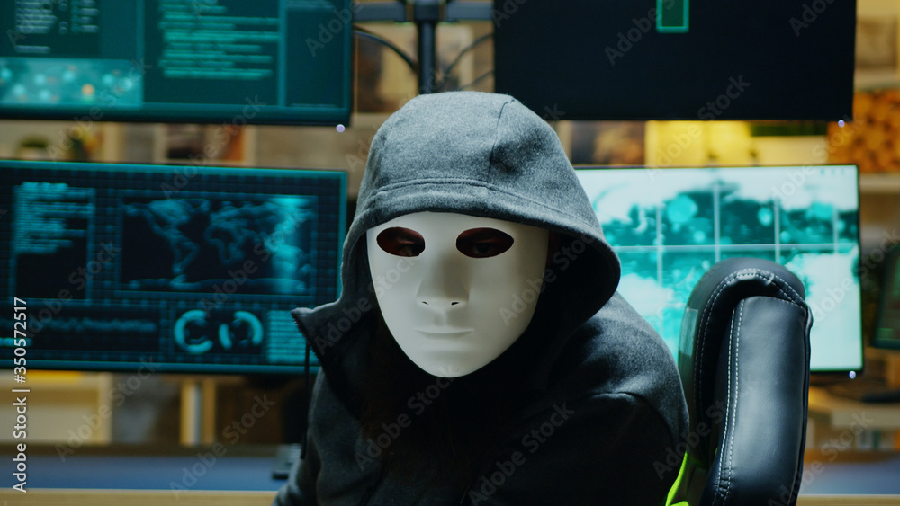 Fototapeta Masked hacker in his apartment looking into the camera while stealing online information.