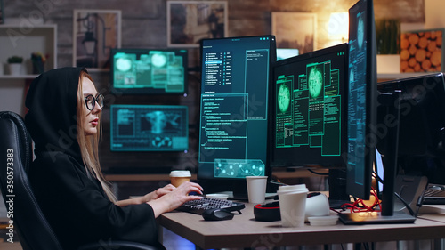 Fototapety, obrazy: Female hacker wearing a hoodie using a dangerous virus to make the government database vulnerable.