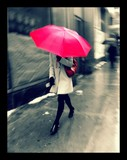 Woman Holding Umbrella And Walking On Street In City