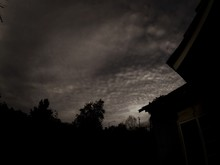 View Of Moody Sky Over Silhouettes Of Trees And House