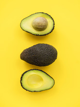 Close Up Of Split Avocado On Yellow Background