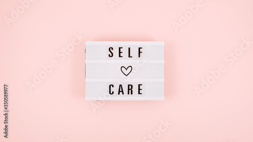 Fototapeta Self-care word on lightbox and flower narcissus on pink background flat lay. Take care of yourself. obraz