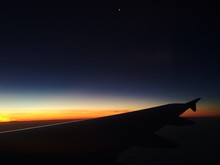 Cropped Image Of Airplane Wing Against Sky During Sunset