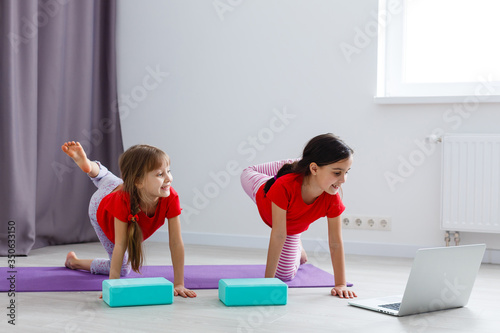 Canvas-taulu two little girls practicing yoga, stretching, fitness by video on notebook