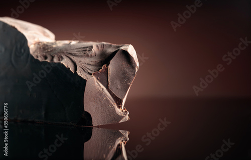 Photo Large piece of dark bitter chocolate on a black reflective background