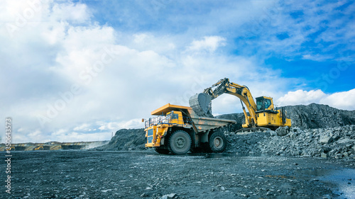 Fotografía Work of trucks and the excavator in an open pit