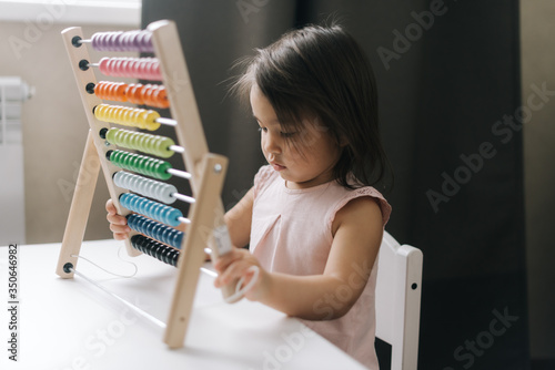 Photo Inquisitive beautiful little girl is playing with multicolored abacus while sitting at the table