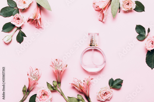 Fototapeta Women's perfume bottle and roses flowers on pink background. Creative Layout, copy space obraz