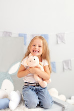 Happy Smiling Toothless Little Blonde Girl. Child Smiling Withouth His Milk Teeth In Children Room. Sweet Little Redhead Girl Is Hugging A Teddy Bear On At Home. Child Plays With A Toy In Kindergarten