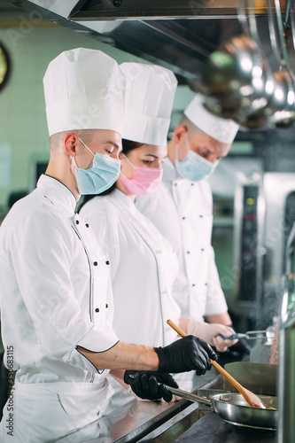 Obraz Chefs in protective masks and gloves prepare food in the kitchen of a restaurant or hotel. - fototapety do salonu