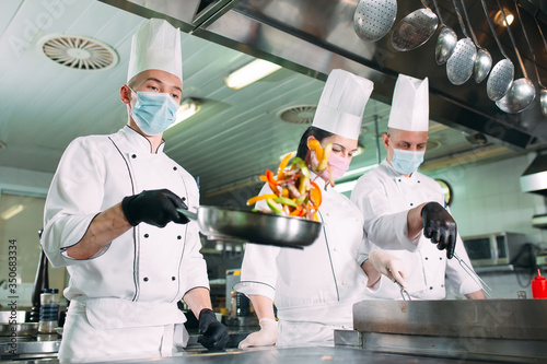 Tablou Canvas Chefs in protective masks and gloves prepare food in the kitchen of a restaurant or hotel
