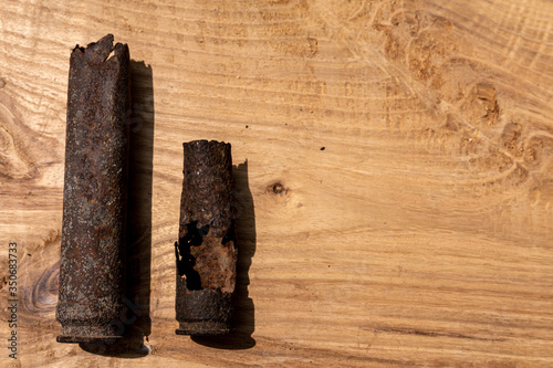 old rusty artillery shell and aircraft projectile on wooden background, shells b Canvas Print