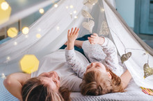 Happy Mother And Little Toddler Girl Lying On The Floor Of Handmade Tent Looking At The Garlands