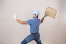 Mexican Courier With Cardboard Box With Arms Outstretched Trowing  Away Package Due To Coronavirus Pandemic