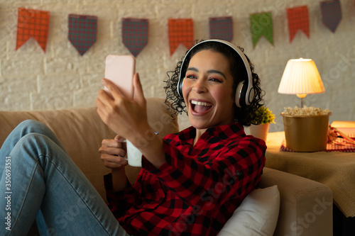 Obraz Cheerful african american woman with headphone smiling with broad smile and using mobile phone Indoors at home living room. Party, weekend, dance, quarantine, concert, music concept. - fototapety do salonu