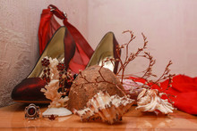 Composition Of Shoes, A Red Dress, Shells, A Mirror, Jewelry, And Dried Flowers On A Wooden Table.