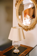 Vintage Antique Table Lamp With White Lampshade And Crystal Base. Antique Mirror In A Gold Frame.