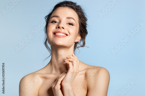 Vászonkép Beautiful brunette  girl with glowing hydrated facial skin touching healthy palm