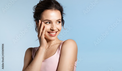 Cuadros en Lienzo Young woman with bare shoulder and shiny glowing perfect face skin laughing timid