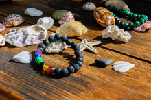 Variety Of Sea Shells On A Rustic Wooden Background With The Bead Bracelets And Starfish Under The Sunlight.