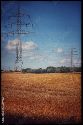 Fototapeta Low Angle View Of Electricity Pylon On Field Against Sky