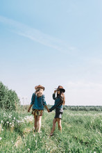 Two Girls In Hats In The Field